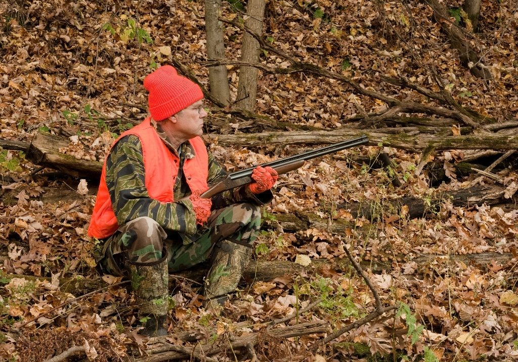 Hunter wearing Camo and Blaze Orange Vest